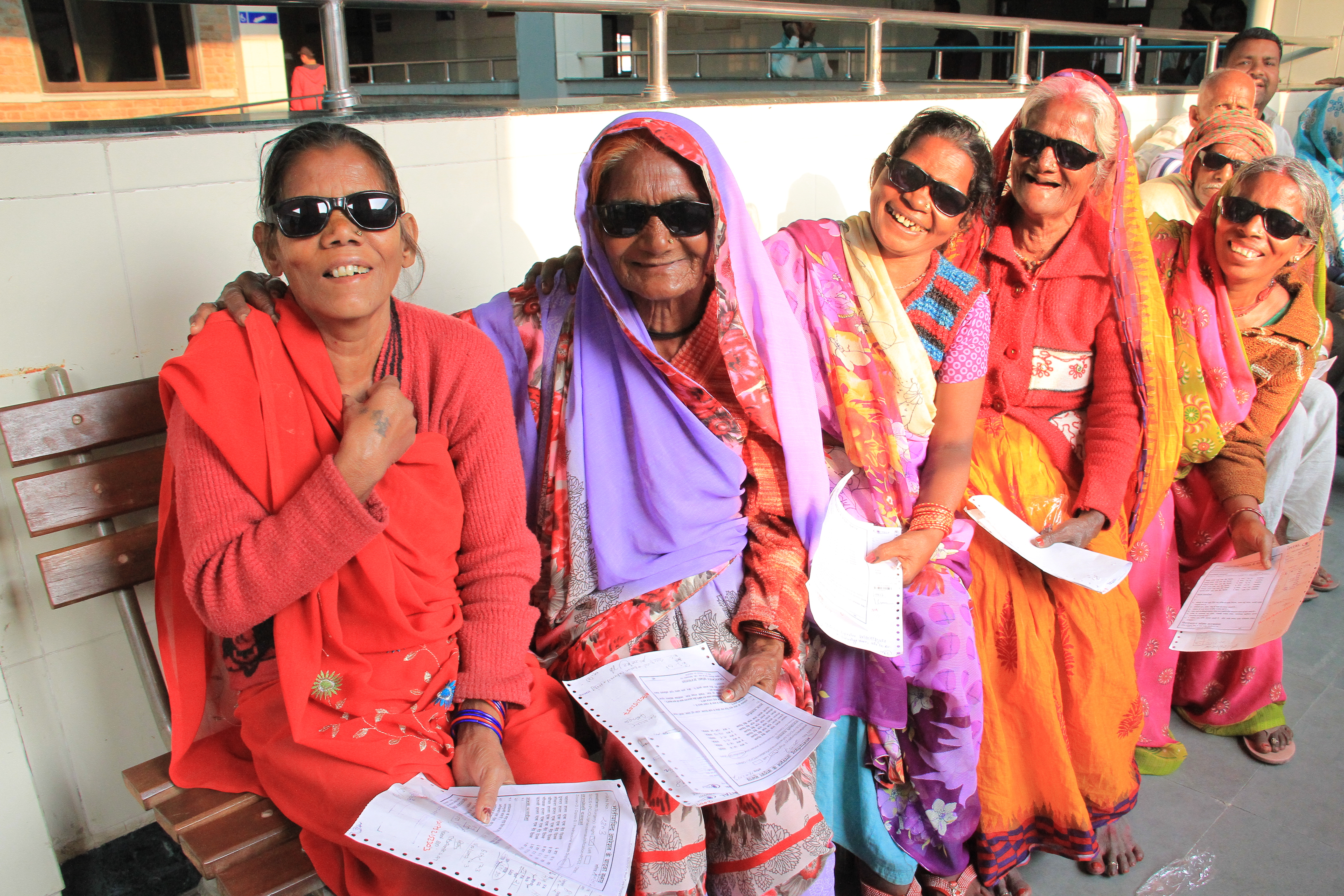 This image shows older women wearing colourful saris and sunglasses, sitting on a bench in a hospital and smiling at the camera.